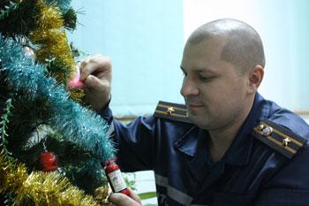 Сергей Рябошапка у спасательской елки в диспетчерской, на которой среди прочих игрушек имеются... маленькие огнетушители.
