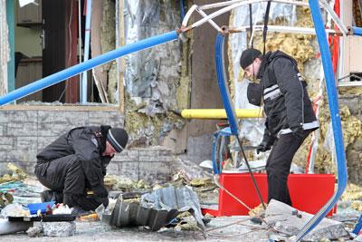 Эксперты собирают улики на месте взрыва у торгового центра Голден Плаза.