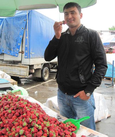Продавец с Крытого рынка Эльмин Джахангиров без опаски ест клубнику сорта Виктория.