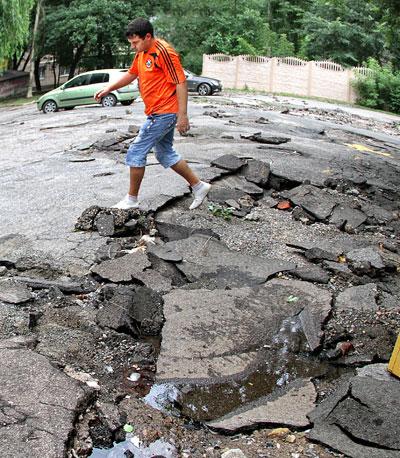 На улице Розы Люксембург ливень оставил после себя следы в виде размытого асфальта и ям на дороге.