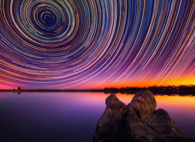 Австралийский фотограф Линкольн Харрисон проявил колоссальное терпение, чтобы снять движение Вселенной. Для получения эффектной картинки он использовал длинную выдержку - до 15 часов, при которой движение звезд по небу отображается в виде полосы.