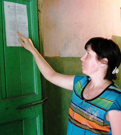 Марина Рудакова показывает отписки начальства, которые украшают двери подъезда.