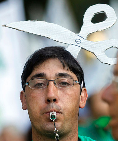 Испанцы к протестам подходят творчески. В Мадриде учитель государственной школы вышел на митинг с ножницами в голове, символизирующими сокращение расходов на образование.