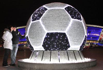 В преддверие праздников гигантский мяч-фонтан у Донбасс Арены превратился в интересное украшение. Его обтянули мишурой, украсили лампочками и подсветили контур каждого прямоугольника светодиодными лентами.