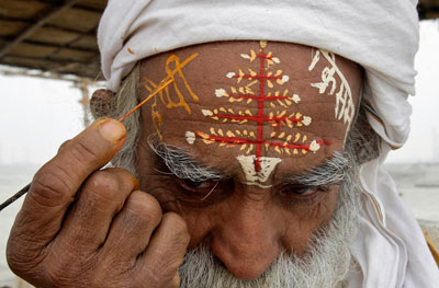 В Индии очень любят Рождество. Старенький индус на языке хинди пишет поздравление прямо у себя на лбу.