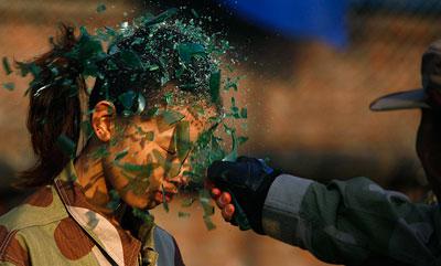 Испытание стеклом. Инструктор разбивает бутылку о голову новобранца во время первой открытой тренировки женщин-телохранителей Китая в Пекине.