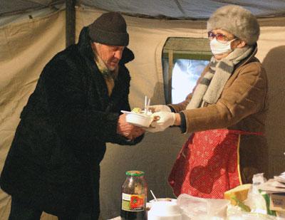 Надежда Бандуркина угощает посетителя порцией горячих макарон.