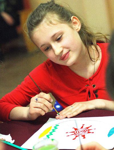 Мариуполь. Воспитанница центра опеки Аня Косарева экспериментирует с цветами для пасхального узора писанки.
