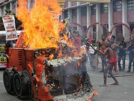 Жители филиппинского племени Ati сжигают муляж бульдозера возле президентского дворца в Маниле, в знак протеста против крупномасштабной добычи полезных ископаемых в регионе их проживания.