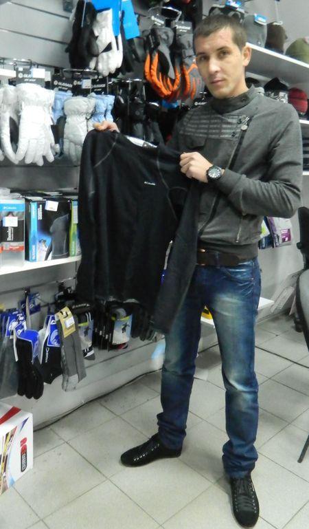 Владимир Чепель демонстрирует покупателям мужскую футболку фирмы Columbia для долгого пребывания на холоде.