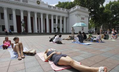 Одесситы пришли под мэрию. Активисты расстелили на Думской площади лежаки, поставили зонтики и расположились загорать. Таким образом они протестовали против того, что вход на 20% пляжей стал платным.