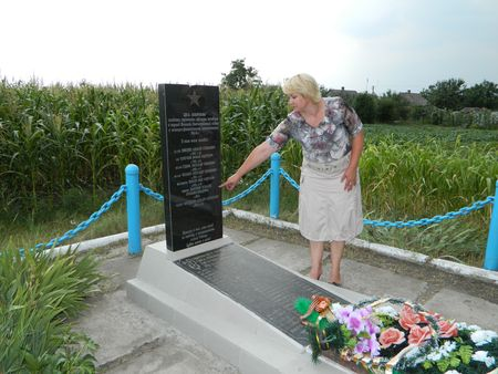 Глава сельского совета Оксана Боровикова показывает новые записи на мемориальной плите у братской могилы.