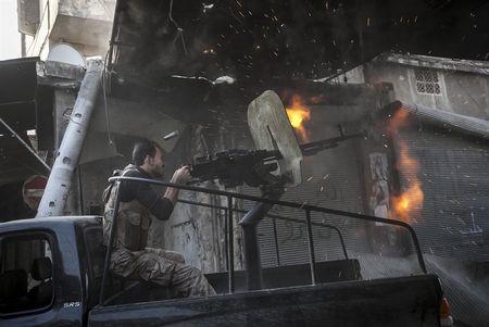 Власти Сирии заявили, что повстанческие отряды активизировались и попытались штурмовать Дамаск, выслуживаясь перед спонсорами - монархиями Персидского залива. В это время в Дохе (Катар) происходил слет лидеров сирийской оппозиции. На фото: повстанец бьет из крупнокалиберного пулемета по правительственным войскам Асада.