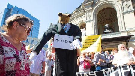 Возле Национальной оперы в Киеве собрались около двухсот обманутых вкладчиков банков и кредитных союзов. Активисты провели акцию протеста с требованием вернуть им их деньги. Они также требовали скорейшего привлечения мошенников к уголовной ответственности.