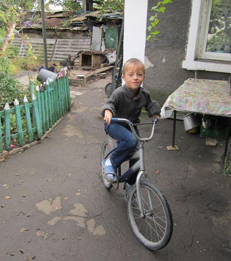 Мужественный Юрка показывает, как он гоняет  на велосипеде.