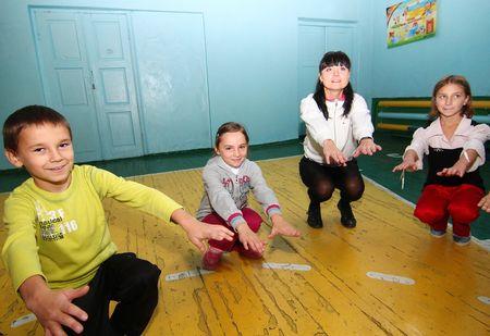 Ученики 5-А класса Никита Назаров, Лера Яшина  и Диана Бондарь с удовольствием делают разминку  на уроке физкультуры с учительницей Еленой Черник.