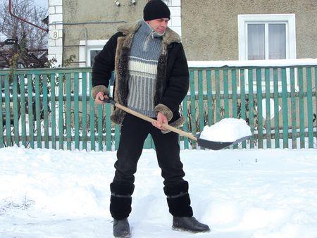 Андрей Овчаренко расчищает площадку  под подъезд своего автомобиля.