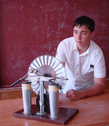 Выпускник Дмитрий Аншаков со всеми приборами в школьном кабинете физики на ты.