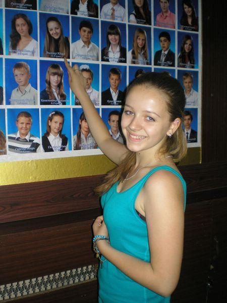 Юлия Лысенко показывает  своё фото, которое уже  несколько лет висит на стенде  «Отличники гимназии».