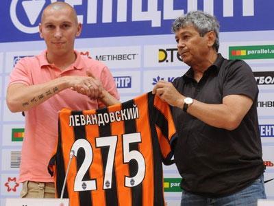Мариуш Левандовский получает от Мирчи Луческу оранжево-черную футболку с числом 275. Это не его  новый игровой номер в «Шахтере» - именно столько матчей  за донецкую команду сыграл футболист сборной Польши.