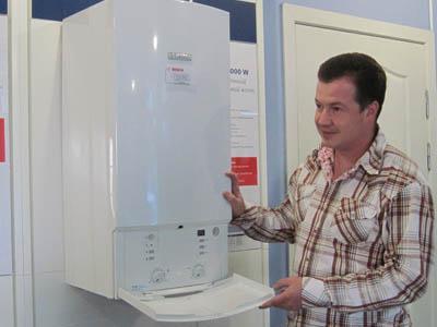 Ярослав Тушевский демонстрирует надежный и экономичный конденсационный котел Bosch.