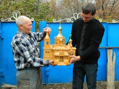 Виктор Конопля показывает молодому сельскому голове Николаю Безгубову макет деревянной церкви, которая стояла в старых Рубцах.