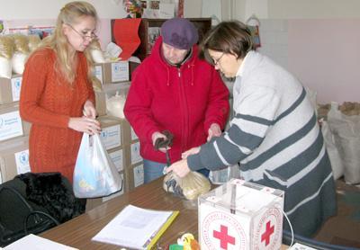 Очередная нуждающаяся в помощи престарелая женщина получает продуктовый набор от главы ДГО ОККУ Инны БОРИСОВОЙ (слева) и медсестры Светланы БРУДИНОЙ.