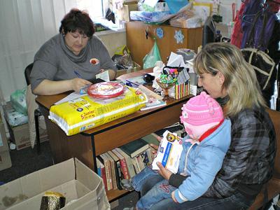 Дончанка Виктория с маленькой дочкой Дашей получают продуктовые наборы и игрушки.