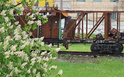 За зелёной декорацией - остовы сгоревших вагонов.