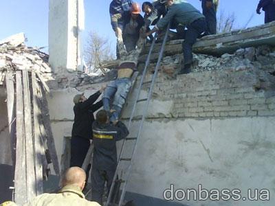 Спасатели вытаскивают тело одного из погибших юных работяг.