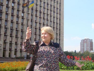 Нина Щербак у здания областной госадминистрации, возле которого рядом с национальным реет ее детище - областной флаг.