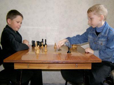 Перед началом тренировки девятилетний Владислав Кулеш и семилетний Ярослав Недоруба разминаются игрой в поддавки.