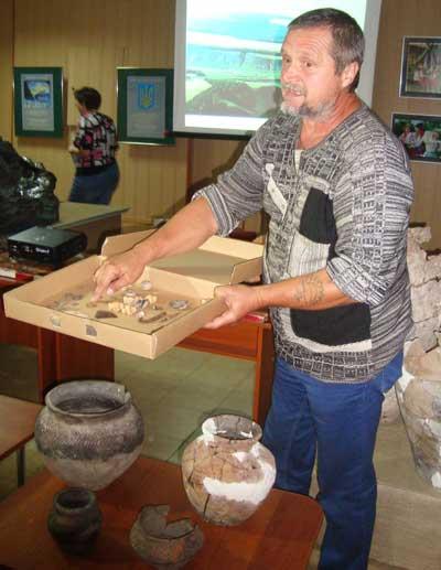 Эдуард Кравченко показывает находки Сидоровского археологического памятника. Перед ним на столике - сосуды, найденные в курганах Попов Яра.