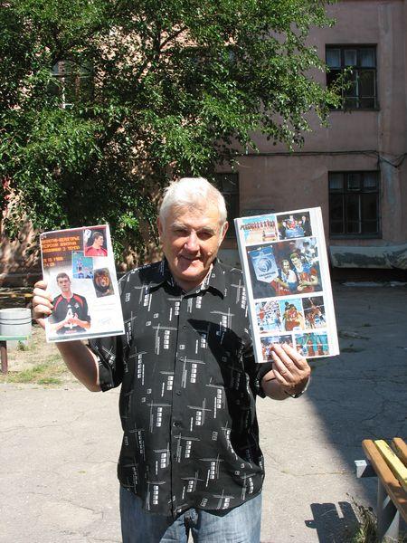 Борис Оснач показывает собранные им фотографии Дмитрия с различных соревнований.